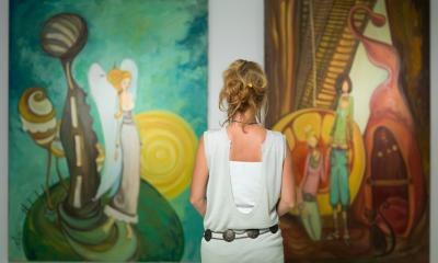 Woman in a grey dress stood with her back to the camera while looking at paintings