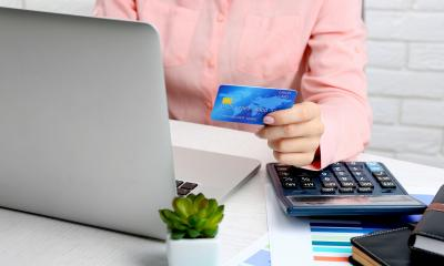 Person in a pink shirt holding a credit card while using their laptop for online sales