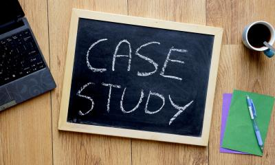 'CASE STUDY' written on a small blackboard next to a laptop and a mug