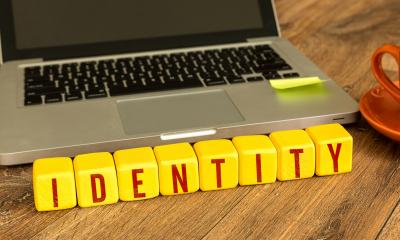 'IDENTITY' written on yellow cubes next to a laptop