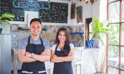 A husband and wife smile for the camera as they open their new venture.