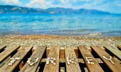 A wooden crate with stones spelling out TURKEY on a beach looking out to sea