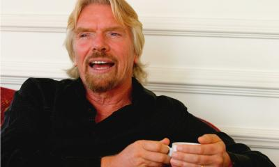 Richard Branson wearing a black shirt while sitting on the sofa holding a mug