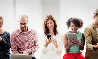 A group of diverse people consume online content on a variety of devices