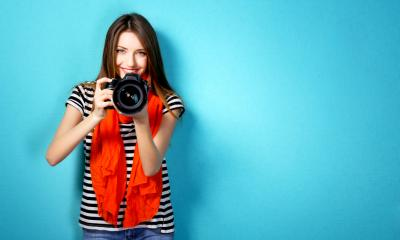 A lady holding a camera stood in front of a blue background