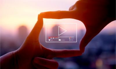 Online live video marketing concept. Photo sign made by human hands on blurred sunset sky as background