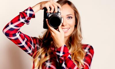 An attractive young woman is using a camera to take a photograph