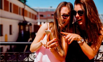 Two women pointing to an advert on instagram on their phone