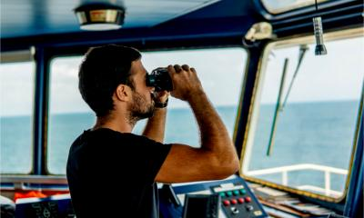 Navigational officer on lookout watch is looking through binoculars.