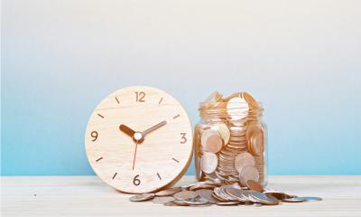Wooden clock leant again a jar filled with coins that are overflowing onto the table