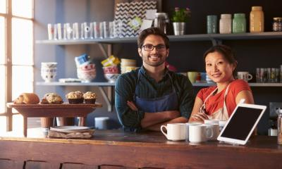 A pair of smiling entrepreneurs stand in their coffee shop and bakery - local business concept.
