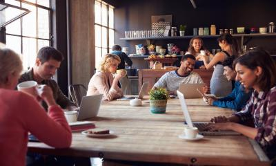 A group of freelance and flexible workers in a remote working cafe