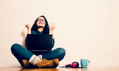 A young woman sits on the floor with her laptop and raises her arms happily - earning money online concept.