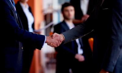 Two men in suits shaking hands and creating a marketing partnership between their small businesses