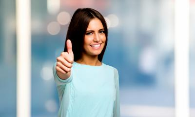 Woman in a light blue top giving thumbs up