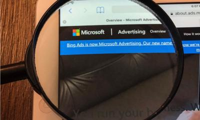 Magnifying glass over an iPad displaying a Microsoft Advertising website