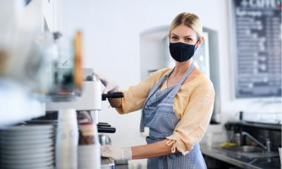 Coffee shop woman owner working with face mask, open after lockdown quarantine