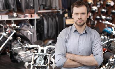 Man in a grey shirt crossing his arms in a motorcycle dealership