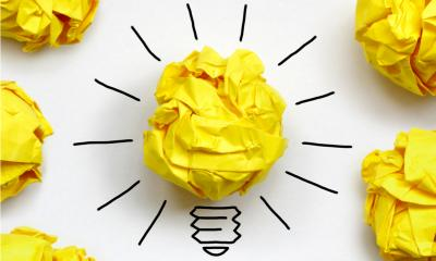 Yellow scrunched up pieces of paper on a white background representing lightbulbs