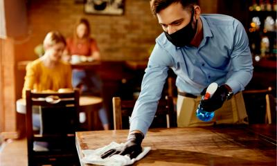 A waiter cleans a cafe table while wearing gloves and a face mask