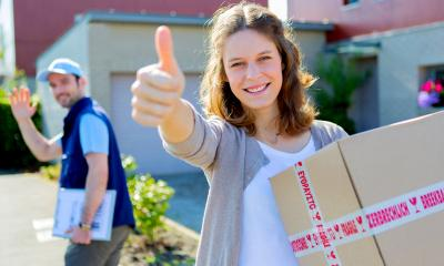 Woman smiling with her thumbs up while holding a cardboard package from an online sale