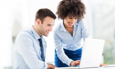 Male and female co-workers review the results of their online marketing