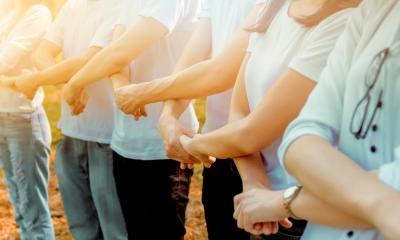 A company team hold hands in an act of solidarity