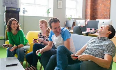 A group of happy business colleagues bond over playing a branded game together.