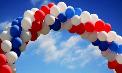 An archway made of red white and blue balloons on a sunny day