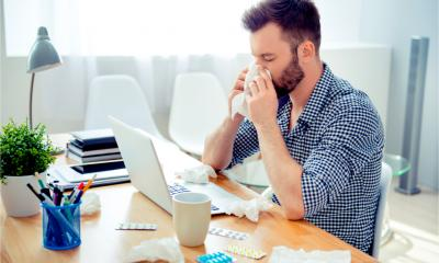 A man displays presenteeism by working whilst unwell
