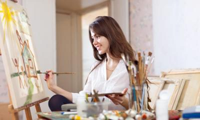 Woman sitting down painting on canvas with paint brushes in foreground