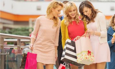 Happy shoppers clutch their bags or shopping