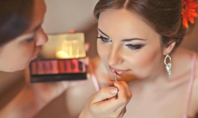 Woman filling other woman's lips in with lipstick in beauty salon
