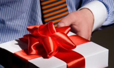 A businessman gives a customer a gift to acknowledge their loyalty