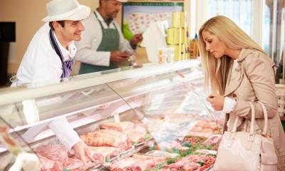 Butcher pointing to a selection of meats whilst serving woman in butchers