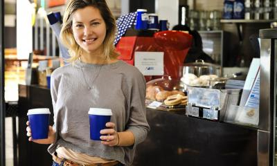 Woman holding two cardboard cups of coffee in front of till