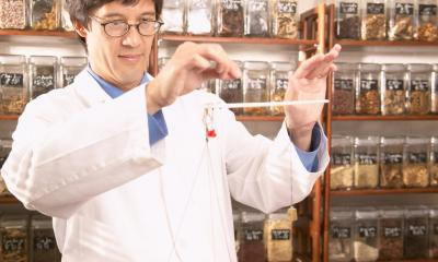 Man with glasses in white lab coat mixing herbs in front of rows of herb jars
