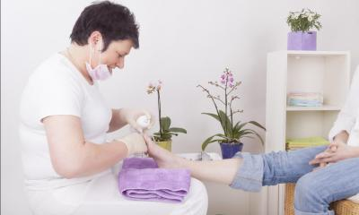 Woman with short hair looking at patients feet in a white room