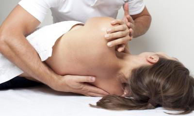Woman lying on her side being moved into position by male chiropractor