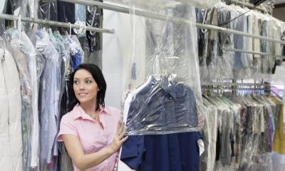 Woman in pink top packing shirts in a dry cleaning store