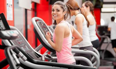 Multiple woman on treadmill jogging in gym with red walls