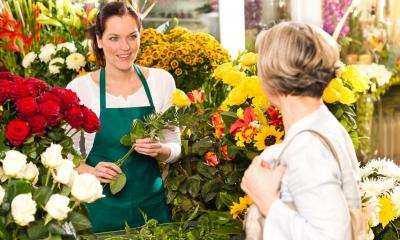 Florist surrounded by various types of flowers serving a customer