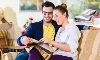 Man and woman sitting on sofa looking at piece of material