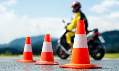 Yellow motorcycle rider driving round three orange and white cones