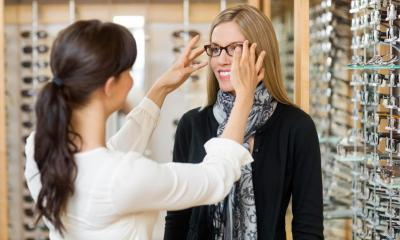 Female optician giving customer pair of glasses in glasses shop