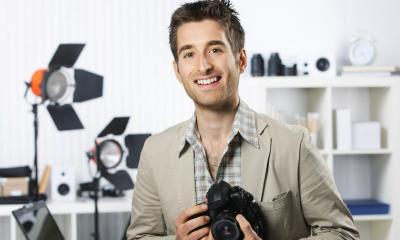 Man in beige suit holding black camera in photo studio
