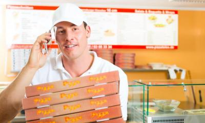 Man on phone holding stack of pizzas in pizza takeaway shop