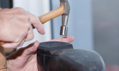 Person hammering nail into the heel of a black shoe