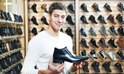 Man holding black shoe in shoe shop with multiple shoes in background