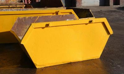 Yellow skips on road outside garages